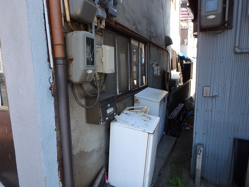 外壁塗装前の傷んだ外壁の店舗ビル側面